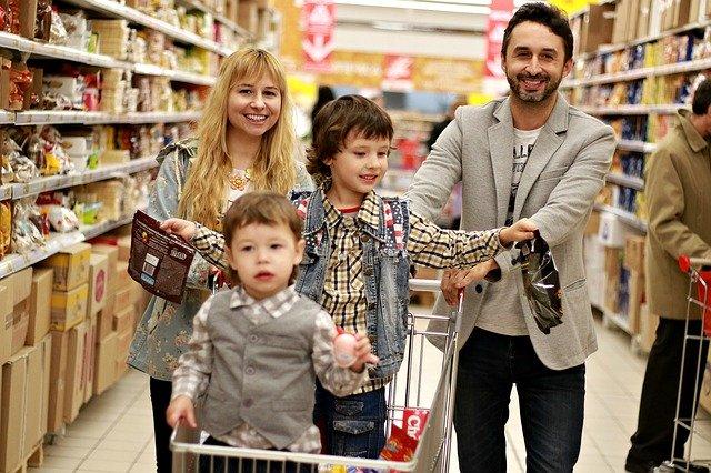 Rodina s nákupním košíkem v obchodě.
