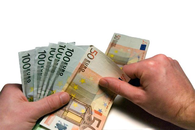 člověk počítající eurobankovky na stole